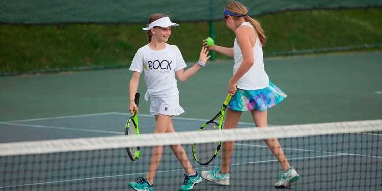 Two girls high-five each other on a tennis court at Rio Mar Country Club